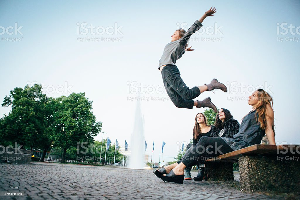 friends sitting together and watching for a jumping woman stock photo