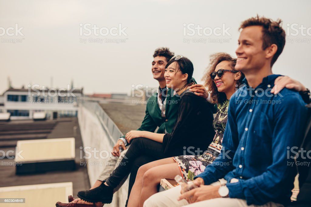 Friends sitting together on rooftop – Foto