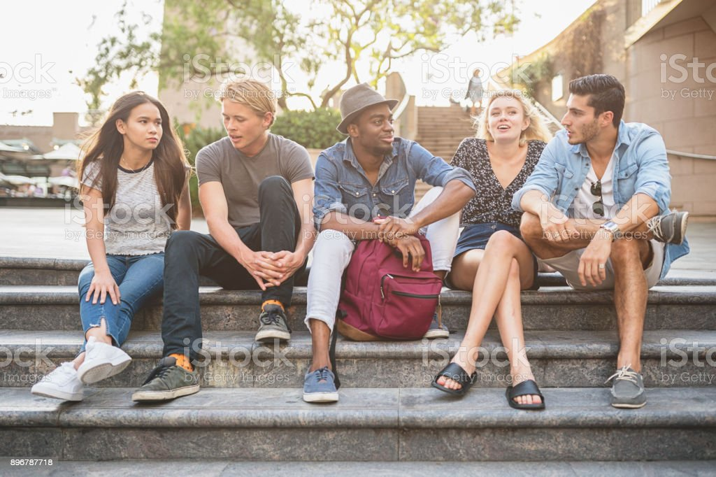 Friends sitting together talking in Darling Harbour Sydney stock photo