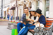 istock Friends sitting together with tablet on the bench 500018670