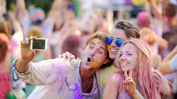 friends smiling and posing for selfie on smartphone, color festival, having fun - concert selfie stock photos and pictures