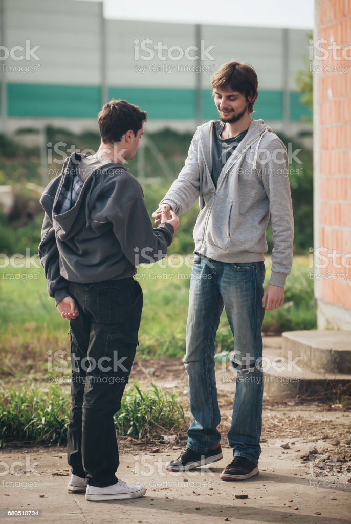 Friends smoke marihuana or hashish joint in underground ghetto neighborhood stock photo
