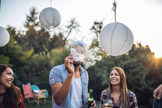 Friends smoking and drinking at a party Young and mixed ethnicity group having fun together, having a party and a gathering, celebrating a birthday. marijuana joint stock pictures, royalty-free photos & images