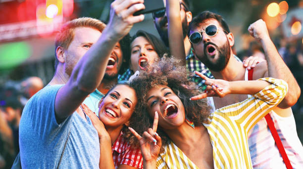 friends snapping selfies. - concert selfie stock photos and pictures