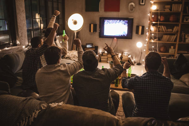 Friends spend weekend together watching TV Group of young men gather at home party. They are watching basketball game on tv, drinking beer, making jokes and cheer for their team. spectator stock pictures, royalty-free photos & images