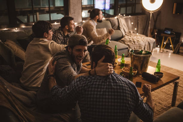 freunden verbringen wochenende gemeinsam vor dem fernseher - spielabend snacks stock-fotos und bilder