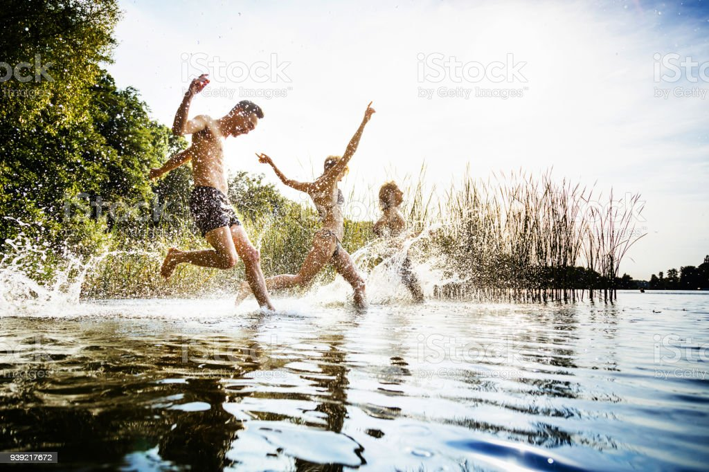Friends Splashing In Water At Lake Together
