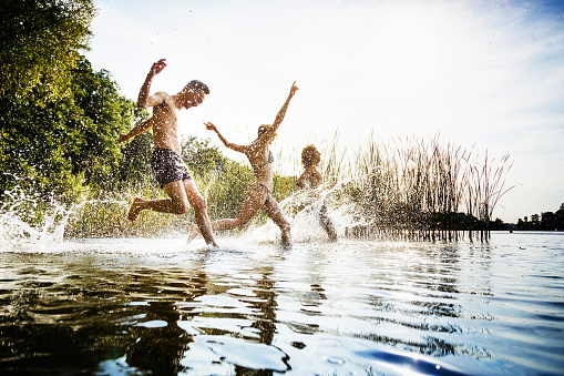 A group of friends excitedly splashing in the water on a day out at the lake together.