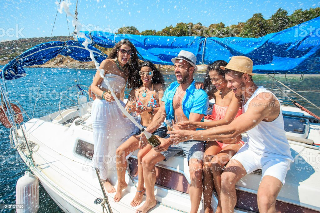 Friends splashing with champagne on yacht stock photo