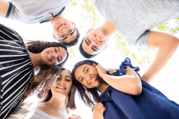 friends standing in a circle outdoors - молодёжная культура стоковые фото и изображения