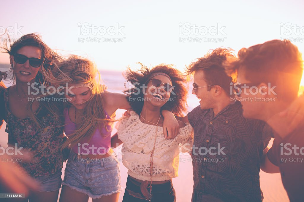Friends standing in a row at a summer evening beachparty stock photo