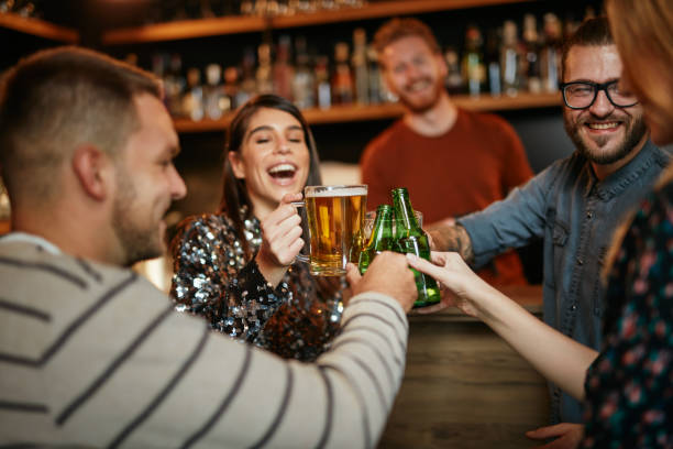 Friends standing in bar and toasting with beer. stock photo