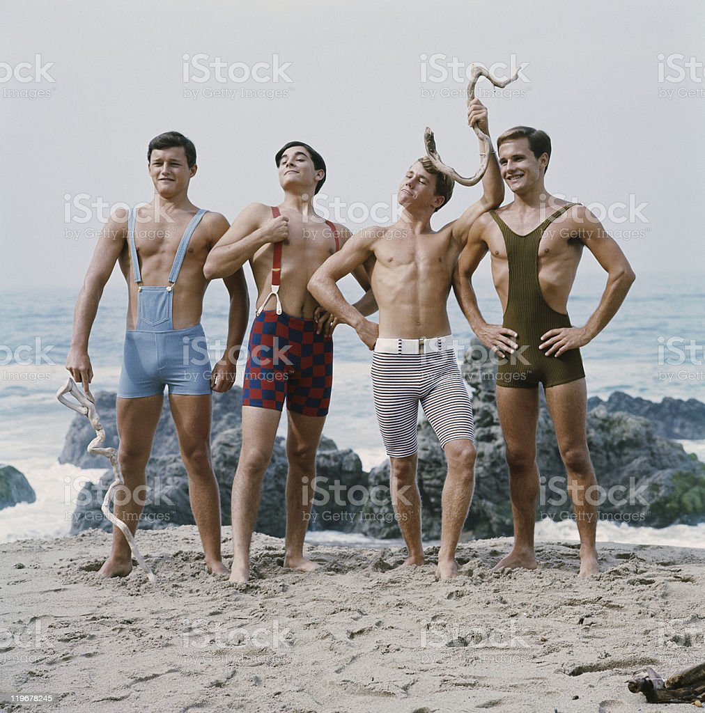 Friends standing on beach, smiling stock photo