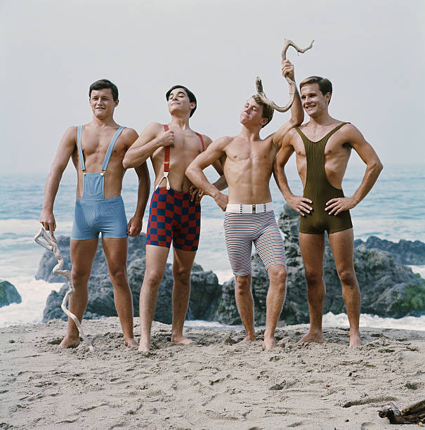 Friends standing on beach, smiling  only young men stock pictures, royalty-free photos & images