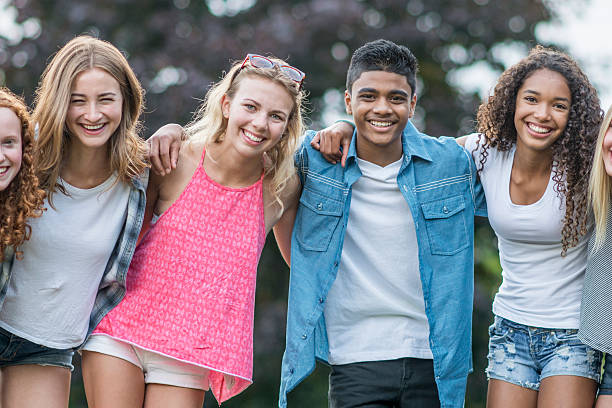 Friends Standing Together Outside A multi-ethnic group of teenagers are hanging out together at the park on a sunny summer day. They are standing in a row and are smiling while looking at the camera. teenagers only stock pictures, royalty-free photos & images
