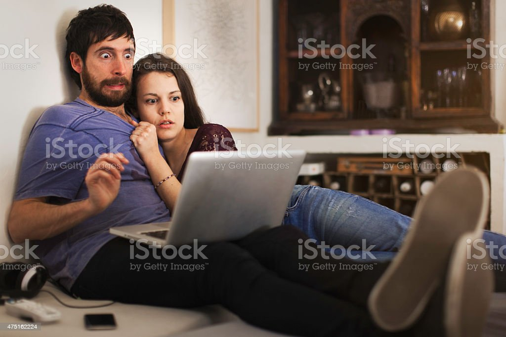 Friends streaming with a laptop a horror film stock photo