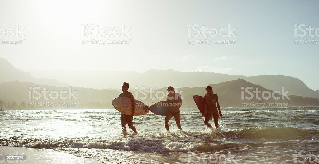 Friends Surfing in the Sunset stock photo