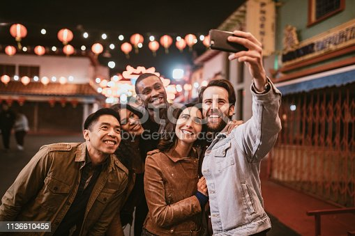A diverse group of multiethnic friends walk the streets of Chinatown in L.A. California on a warm evening, exploring the cities night life.  Bright traditional lanterns illuminate the scene.  They take a smartphone self portrait to share on social media.