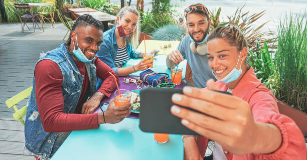 friends takeing selfie in a bar restaurant with face mask on in coronavirus time - young people having fun with drinks and snacks outside with new rules after virus break - covid restaurant imagens e fotografias de stock
