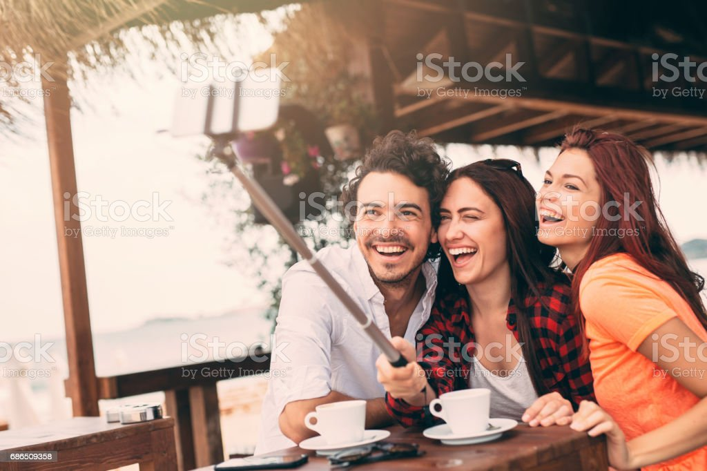 Friends taking a selfie at a beach bar foto stock royalty-free
