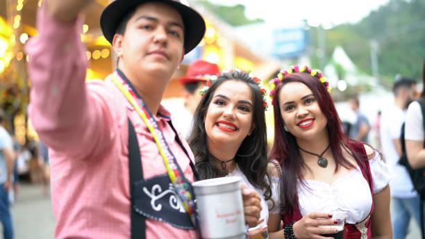 freunde nehmen eine selfie auf dem oktoberfest in blumenau, santa catarina, brasilien - moderne dirndl stock-fotos und bilder
