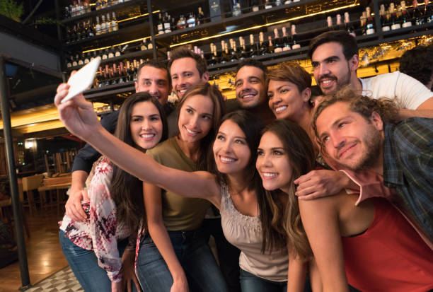 friends taking a selfie at the bar - reunion stock photos and pictures