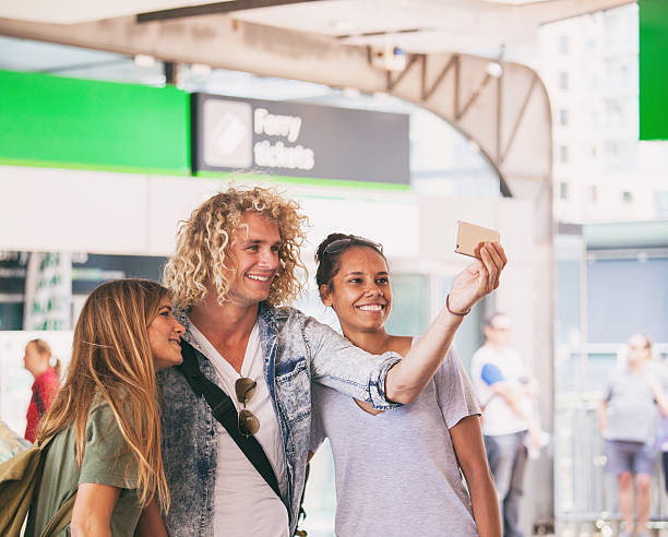 friends taking a selfie before they depart Friends out taking a selfie by the ferry port in Sydney. depart stock pictures, royalty-free photos & images