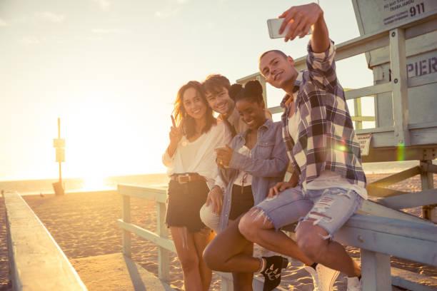 vänner tar en selfie under en fest på stranden i santa monica - los angeles - badvaktshytt bildbanksfoton och bilder