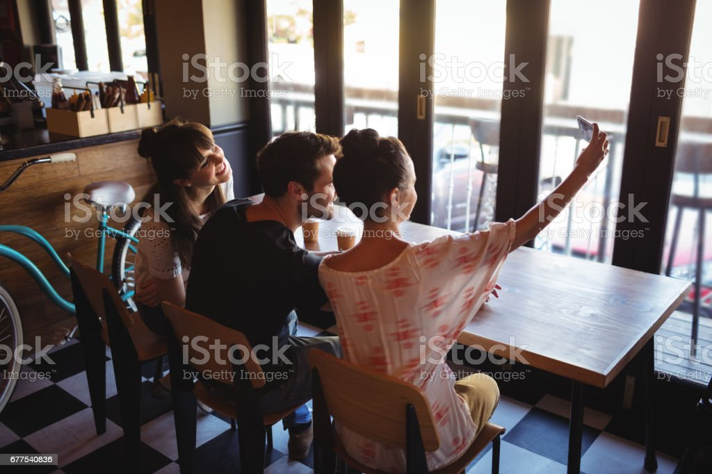Friends taking a selfie on mobile phone royalty-free stock photo