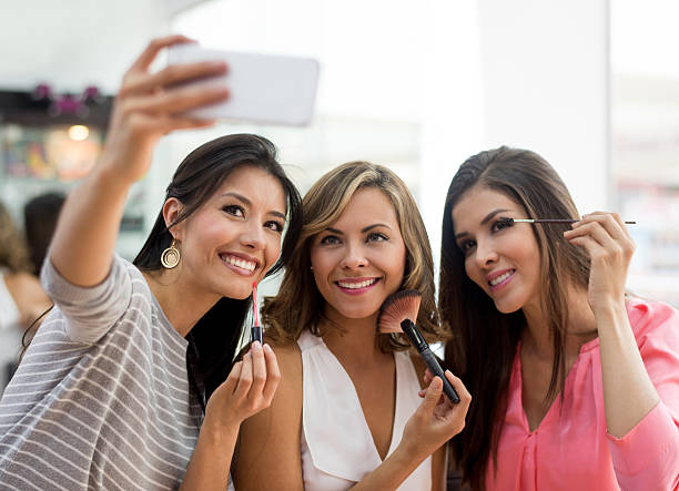 Friends taking a selfie while applying makeup stock photo