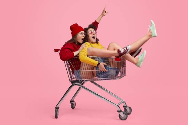 Friends taking part in shopping trolley race stock photo