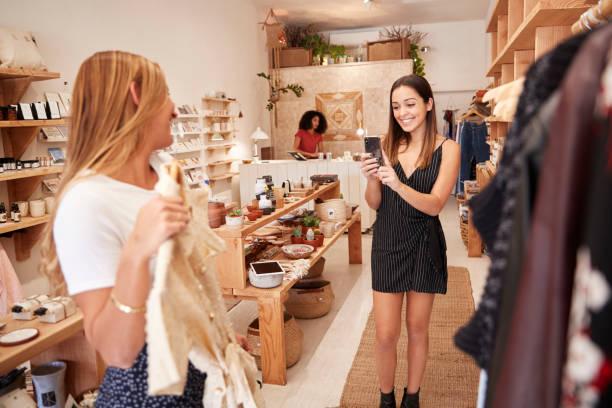 freunde machen fotos auf handy, wie sie kleider im unabhängigen fashion-store wählen - dresses online shop stock-fotos und bilder