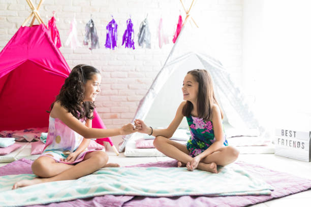 friends taking pinky promises while sitting on duvets against tipis - pinky promise stock photos and pictures