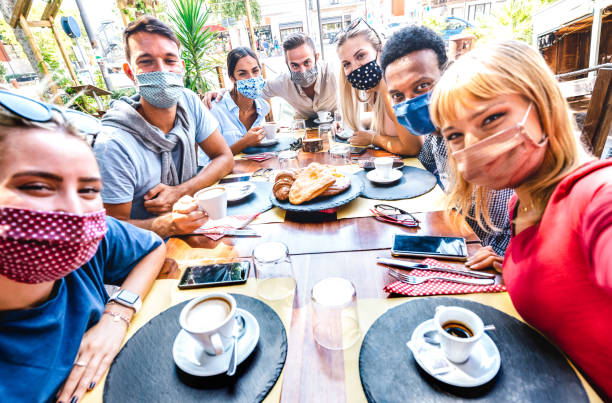 Friends taking selfie at coffee bar - People having fun together at cafeteria covered by face masks - New normal lifestyle concept with happy guys and girls at restaurant cafe - Bright vivid filter stock photo