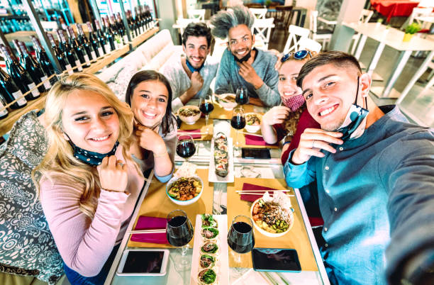 Friends taking selfie at sushi bar restaurant - New normal lifestyle concept about young people having fun together at fashion diner with open face masks - Bright saturated filter - Focus on right guy stock photo