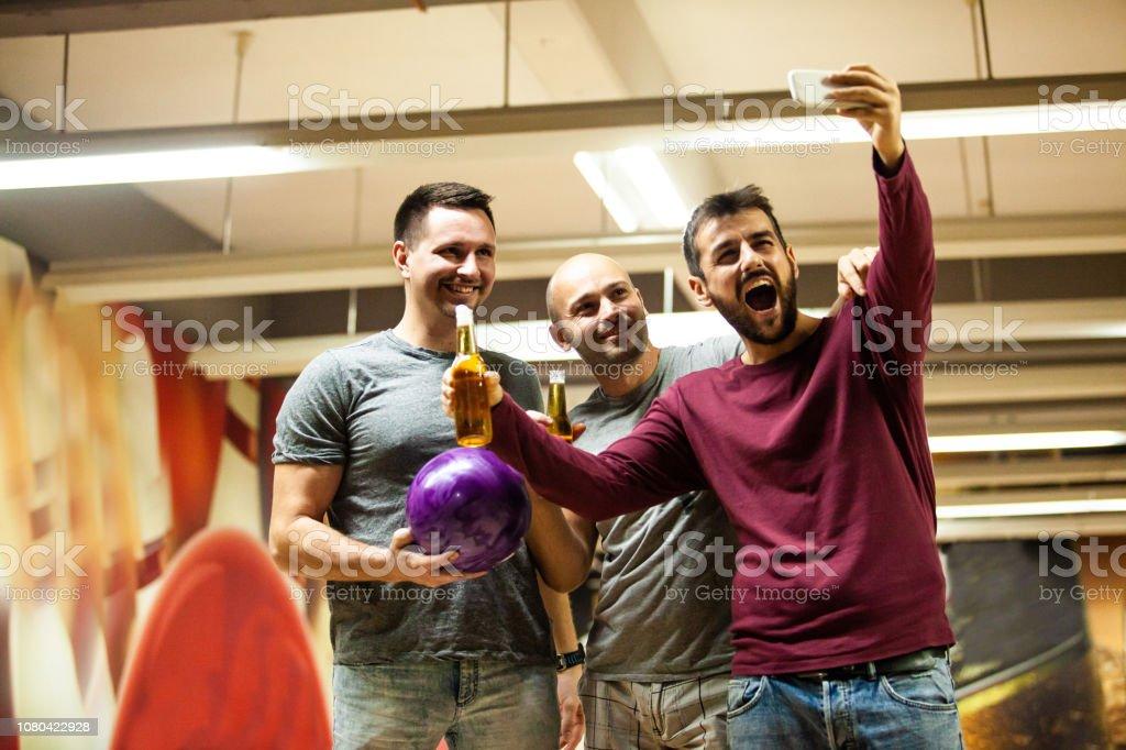 Friends taking selfie in bowling alley stock photo
