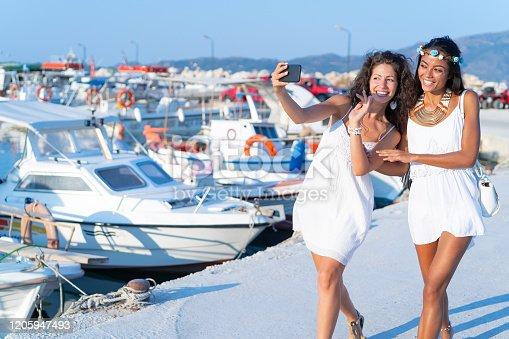 Friends taking selfie on harbor in Zakynthos Greece