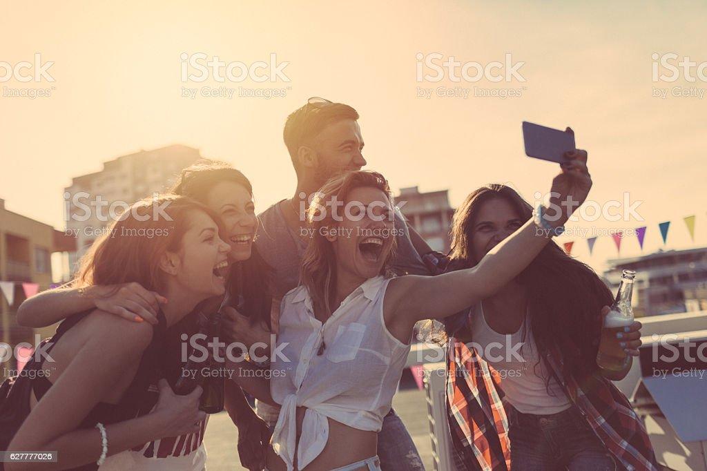 Friends taking selfie on rooftop terrace stock photo