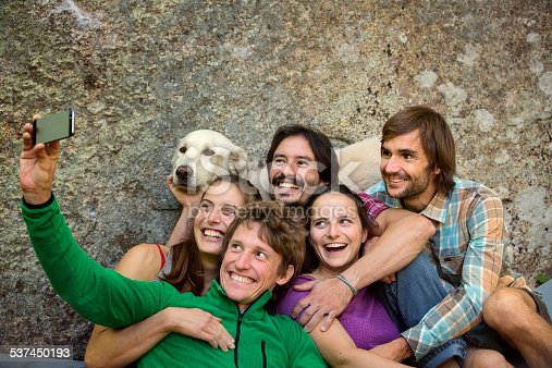 istock Friends taking selfie with dog against rock 537450193