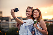 Cheerful young women taking selfie while eating ice cream in the city during sunset.