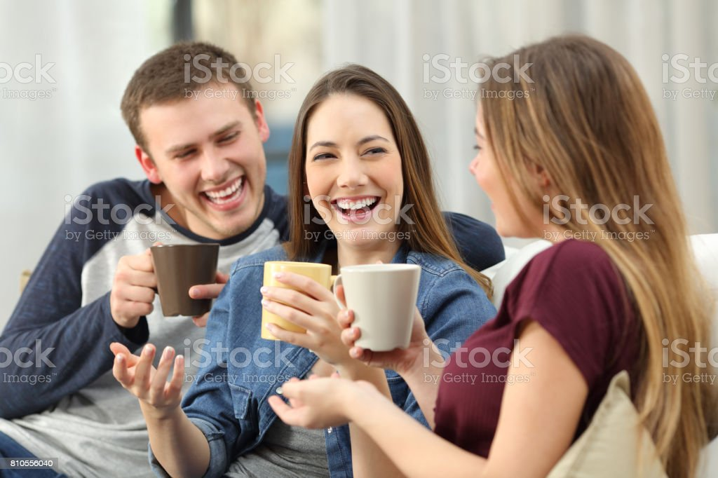 Friends talking and laughing loud at home stock photo