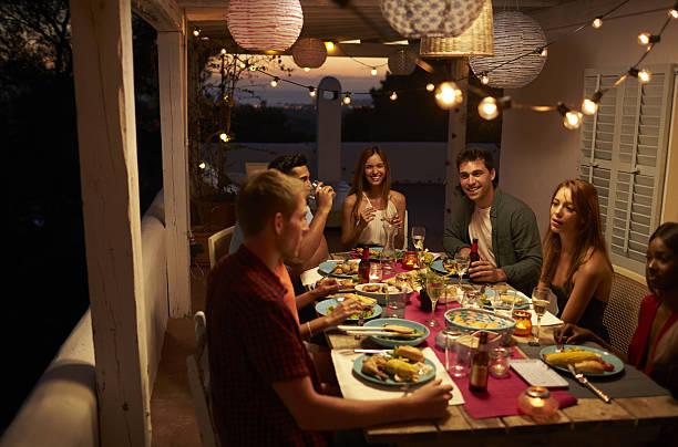 friends talking at a dinner party on a patio, ibiza, spain - terrassen lichterketten stock-fotos und bilder