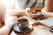 お友達とカフェのテーブルでコーヒー休憩中に話しています。認識できない男性と女性の同僚のビジネス上の問題を議論するコーヒー カップ ソーサーと小さじに焦点を当てる