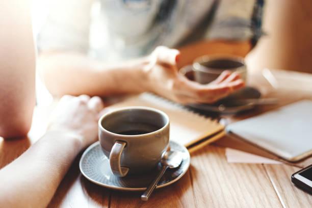 przyjaciele rozmawiają przy kawiarni przy stoliku podczas przerwy kawowej. nierozpoznawalni koledzy i koledzy omawiający kwestie biznesowe, koncentrujący się na filiżance kawy ze spodkiem i łyżeczką - dwie osoby zdjęcia i obrazy z banku zdjęć