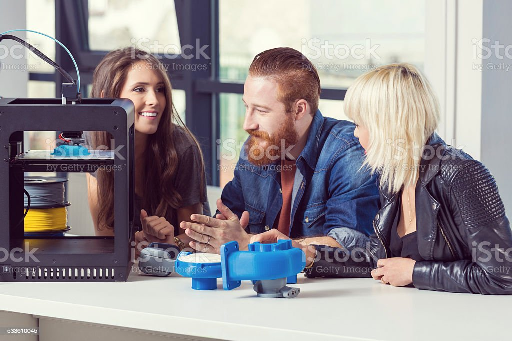 Friends talking in 3D printer office Bearde man sitting at the table in an office and  talking with his two female friends about 3D printer technology. 2015 Stock Photo