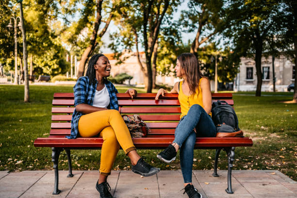 Friends talking on bench stock photo