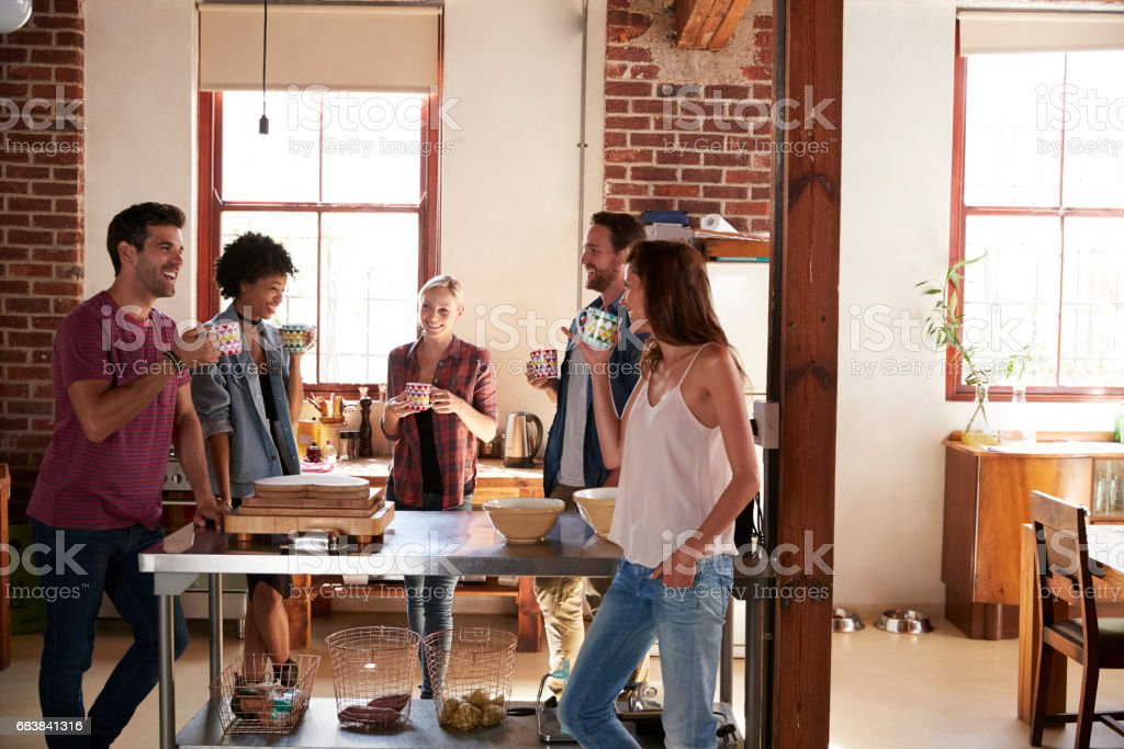 Friends talking over coffee in kitchen, three quarter length stock photo