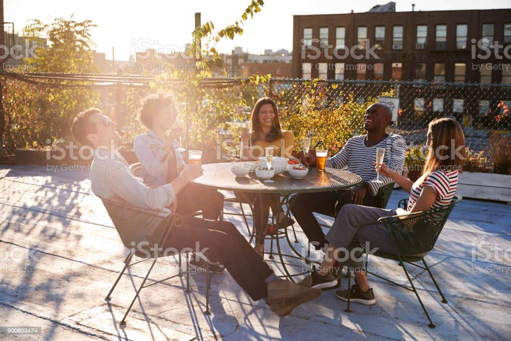 Friends talking over drinks on a New York rooftop - foto stock