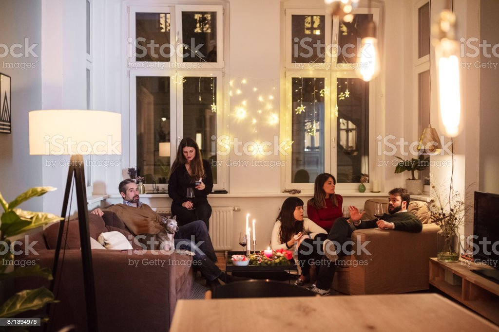 friends talking while sitting in living room during christmas party