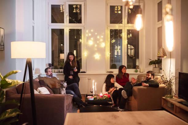 freunde sprechen beim sitzen im wohnzimmer während der weihnachtsfeier - partyraum stock-fotos und bilder